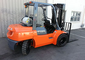 gray and orange forklift warehouse